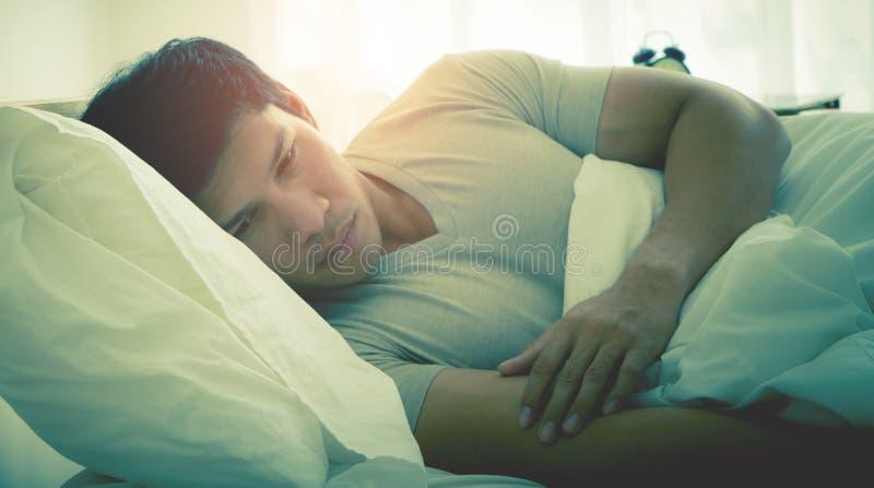 Druk de mens liggende recente ochtend op bed in royalty-vrije stock foto