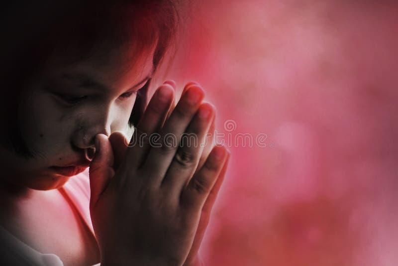 Druk en het droevige kind bidden voor hulp in, zittend in de hoek stock afbeelding