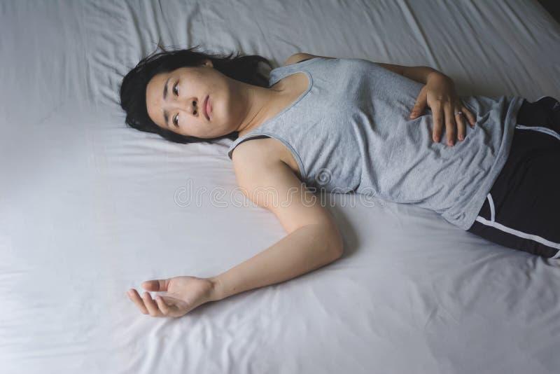 Druk en het hopeloze vrouw leggen op bed in stock foto's