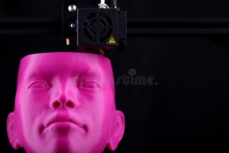 Drukarka 3D produkuje humanoidalną głowę z różowego tworzywa sztucznego w ciemnym otoczeniu — widok z przodu, przestrzeń na tekst obraz royalty free