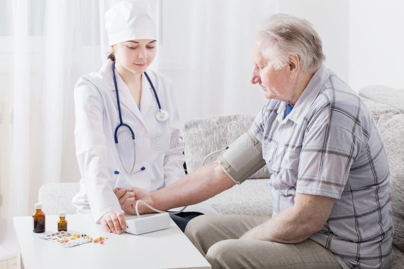 Drukmeting in bejaarden stock foto