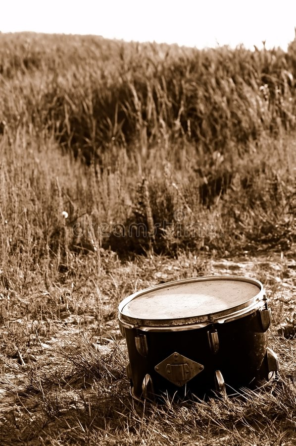 Drum in the field. Lonely disused drum laying in the grass stock images