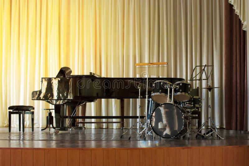 A drum set on a black piano background in a concert hall. A drum set on a black piano background in a concert hall stock photography