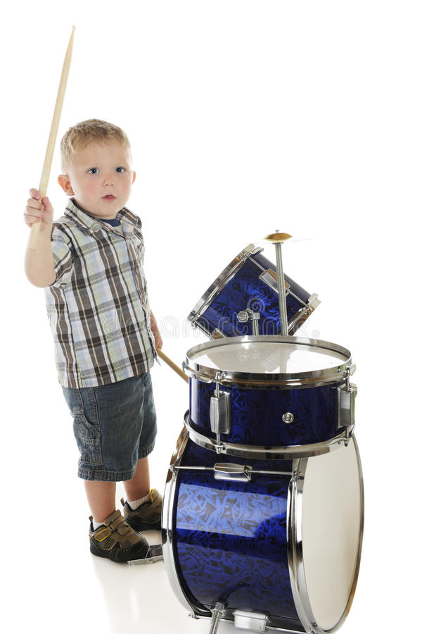 Drummer from Above. A high view of an adorable preschool drummer. Motion blur on upper drumstick. On a white background stock images