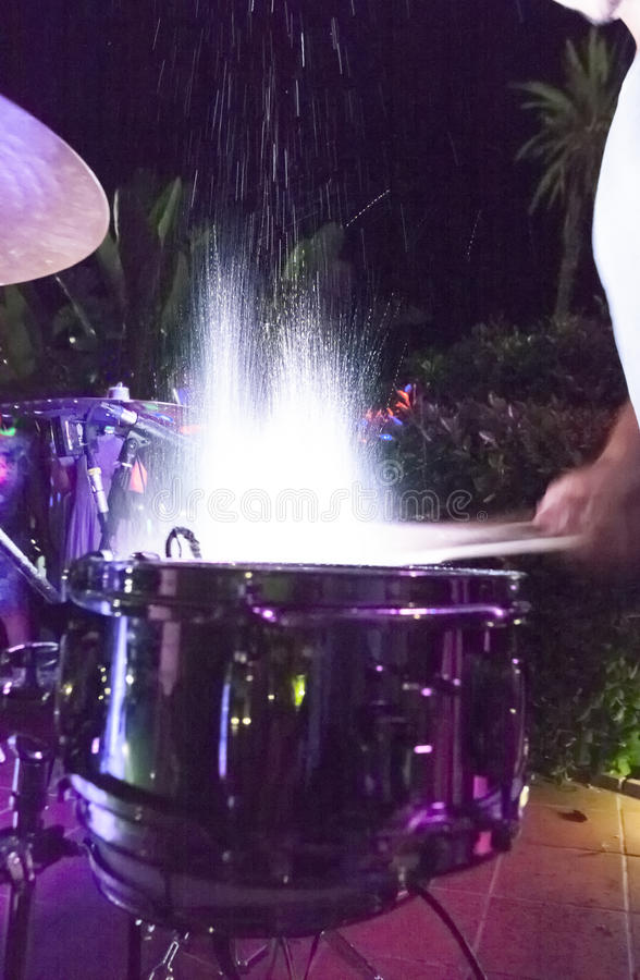 Drummer beating and splashing drums at night show stock image