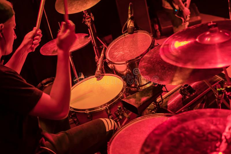 Drummer at the concert. Drummer beats the drums at a concert in red light stock photo