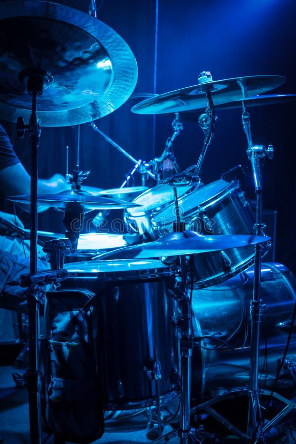 Drummer at the concert. Drummer plays drums, side view, with blue concert lighting stock images