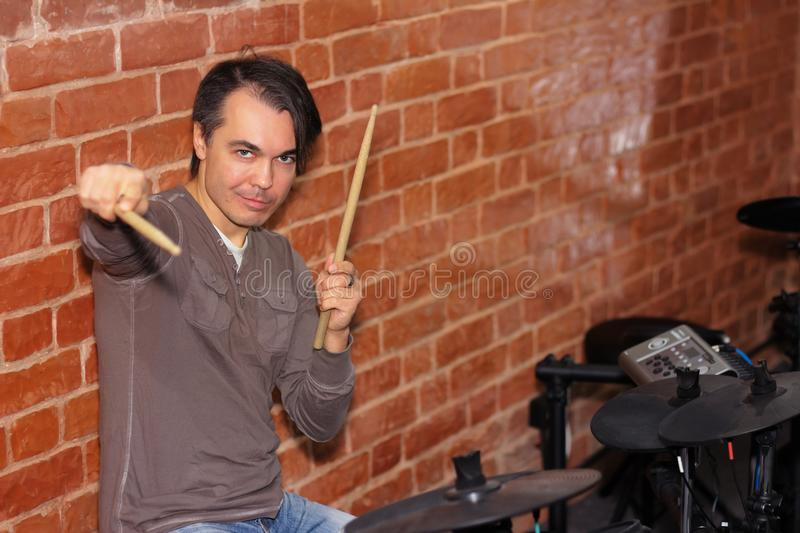 Drummer with drum sticks in his hands playing electronic drums i royalty free stock photography