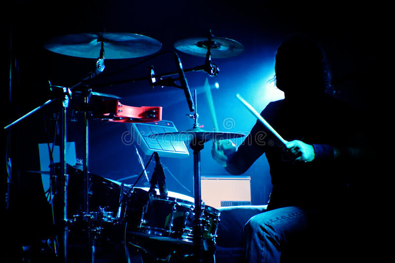 Drummer on a gig. Drummer playing drums in concert with silhouette and backlighting royalty free stock image