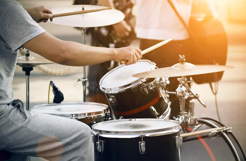The drummer in gray clothes plays on a drum set with wooden drumsticks. The drummer in gray clothes plays on a black and red drum set with wooden drumsticks. He royalty free stock image
