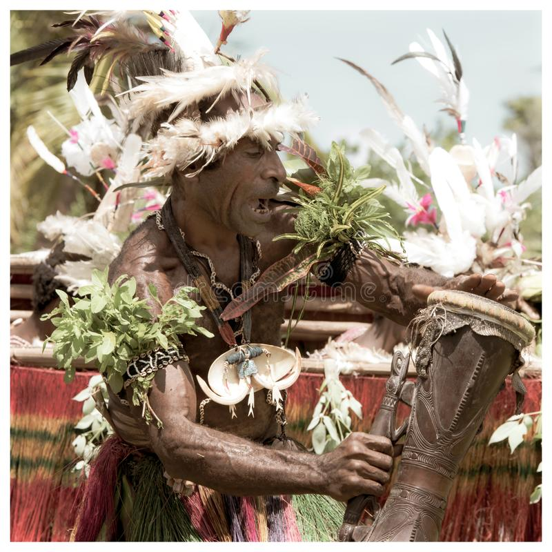 Drummer on impressive dance ceremony, Papua New Guinea. Old photo style in square stock photography
