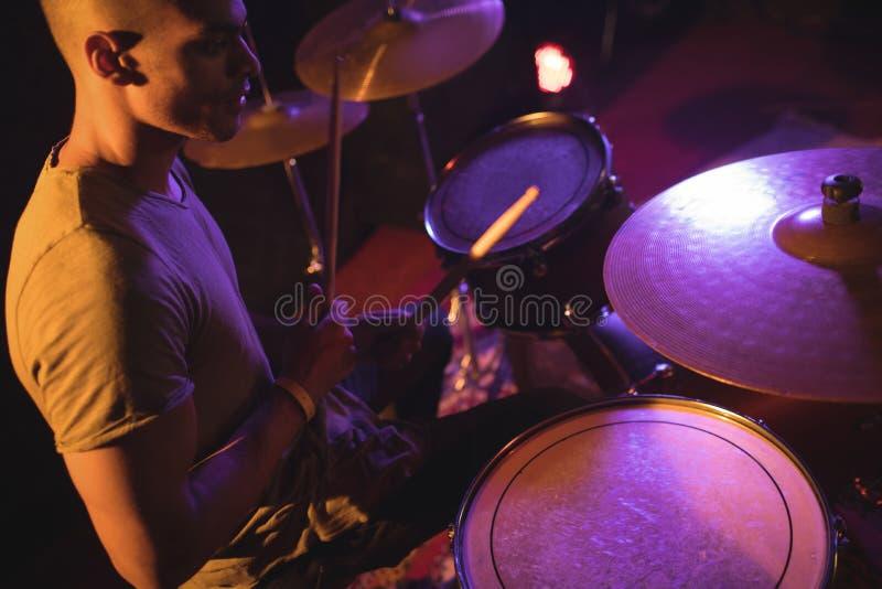 Drummer playing in illuminated nightclub royalty free stock image