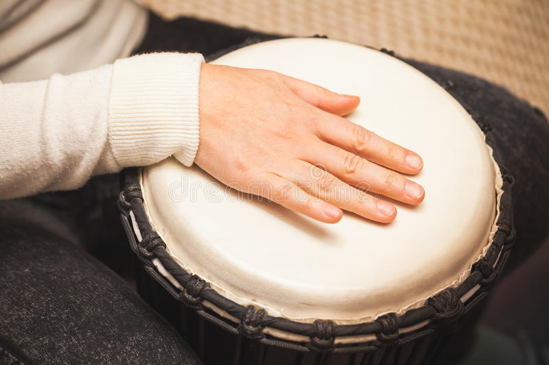Drummer plays on African drum stock photography