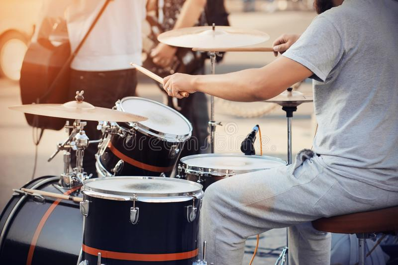 A drummer plays a cool drum kit drumsticks at a concert with the band. A skilled drummer in gray clothes plays a cool drum kit wooden drumsticks at a concert royalty free stock images