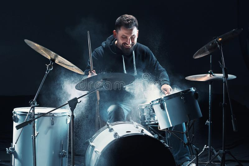 Drummer rehearsing on drums before rock concert. Man recording music on drum set in studio. With show effect in the form of flour stock photography