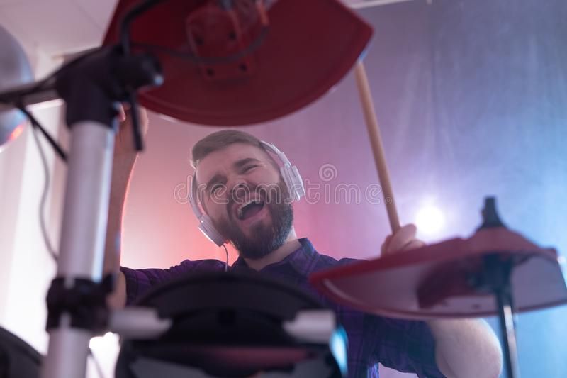 Drums, music and people concept - emotional man playing on elecronic drums, it`s his hobby stock photo