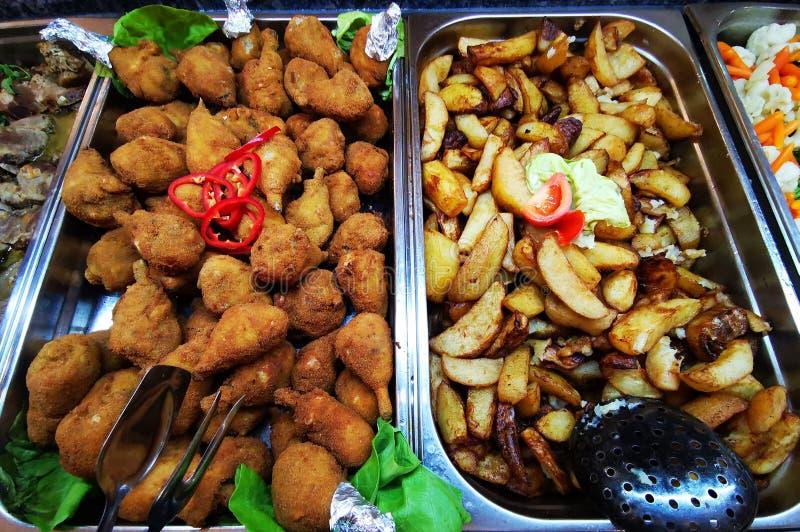 Drumsticks жареной курицы и деревенские картошки стоковая фотография rf