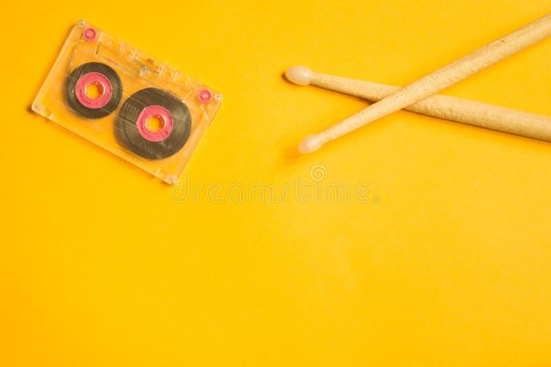 Drumsticks и магнитофонная кассета на желтой предпосылке стоковые изображения