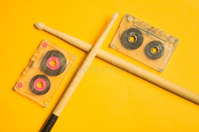 Drumsticks и магнитофонная кассета на желтой предпосылке стоковые изображения rf