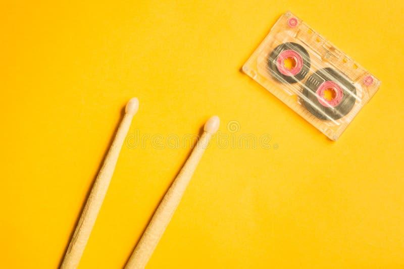 Drumsticks и магнитофонная кассета на желтой предпосылке стоковое изображение