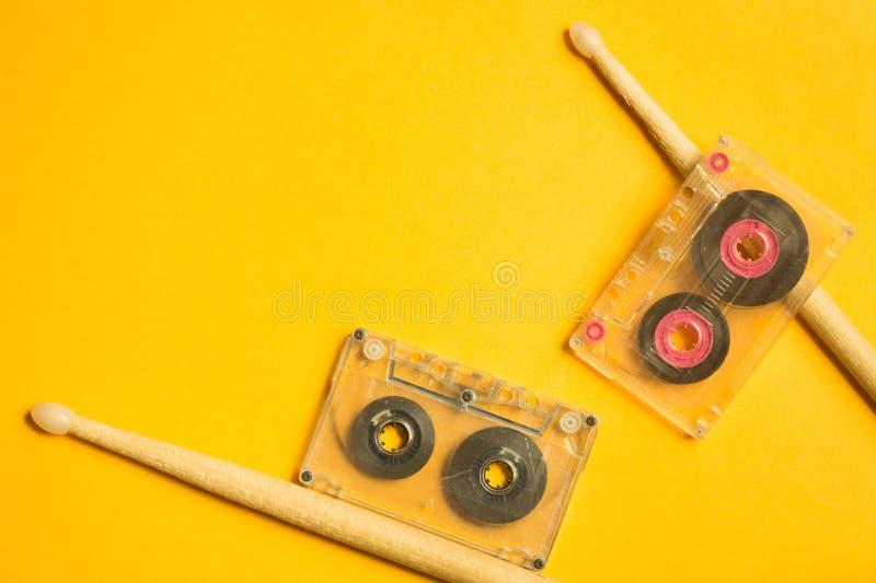 Drumsticks и магнитофонная кассета на желтой предпосылке стоковое изображение rf