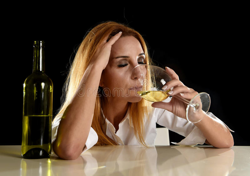 Drunk alcoholic blond woman alone in wasted depressed drinking from white wine glass stock image