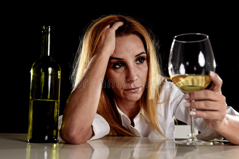 Drunk alcoholic blond woman alone in wasted depressed looking thoughtful to white wine glass. Drunk blond woman alone in wasted depressed expression looking stock image