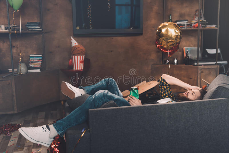 Drunk bearded young man with closed eyes lying on couch royalty free stock photos