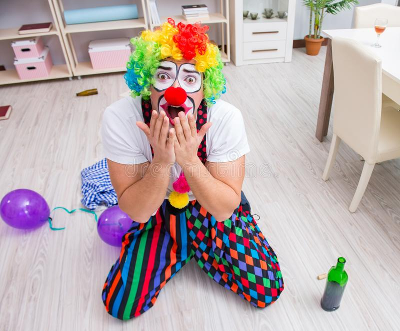 Drunk clown celebrating having a party at home. The drunk clown celebrating having a party at home royalty free stock photography