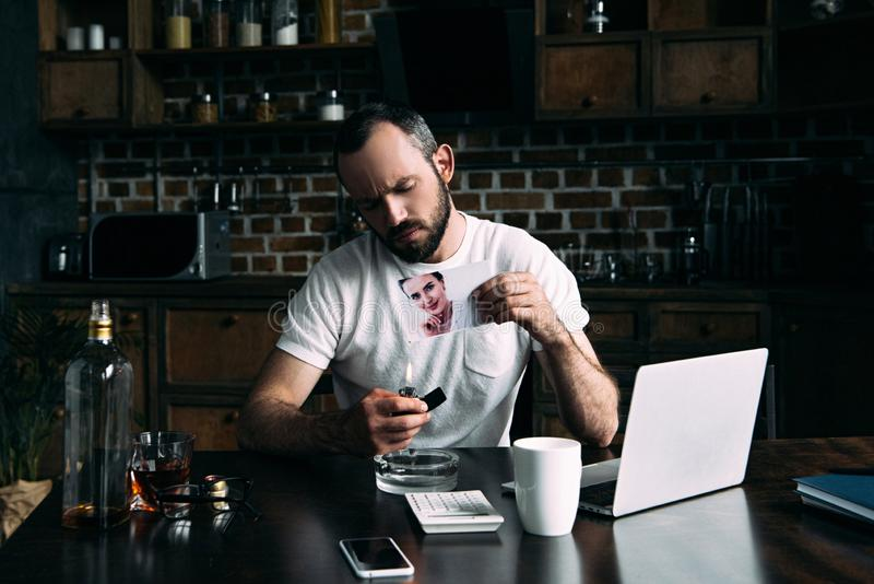 drunk depressed young man burning photo of ex-girlfriend royalty free stock photos