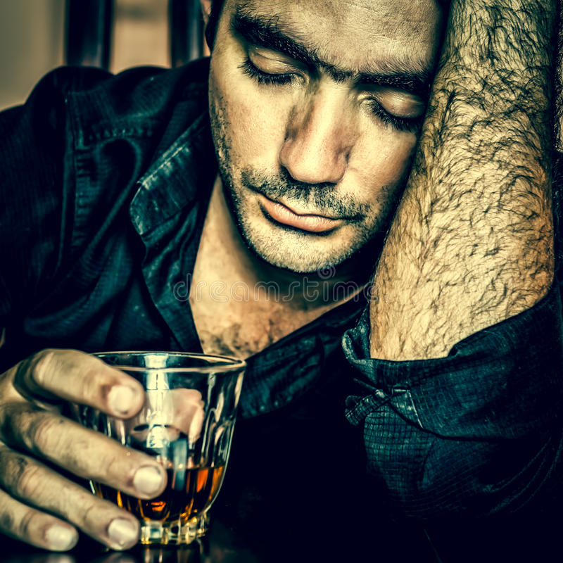 Drunk and desperate hispanic man. Alcoholism : Grunge blue toned portrait of a lonely and desperate drunk hispanic man royalty free stock images