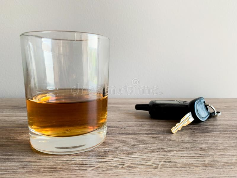 Drunk driving concept. Glass with whiskey and car key on the table. stock photography