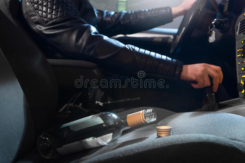 Drunk driving concept. Young man driving car under influence. Drunk driving concept. Young man driving car under the influence of alcohol. Empty bottle of wine stock image