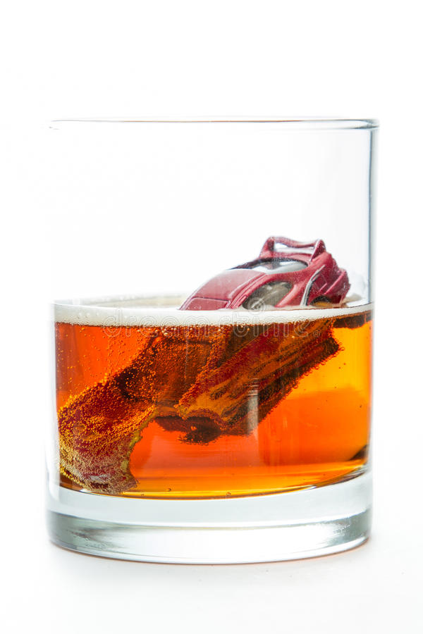Drunk driving. DUI concept. Image of a drunk driving accident inside a small glass with beer isolated on a white background royalty free stock photo