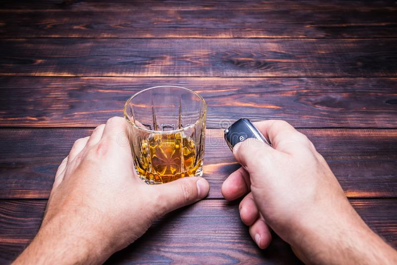 Drunk driving. Glass in man hands and car keys. Drink. Drunk driving. Glass in man hands and car keys. Drink and auto keys stock images