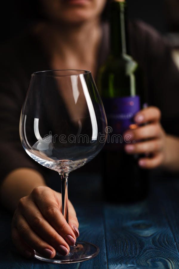 Drunk female with bottle of alcohol. Soccial issue alcoholism. stock photo