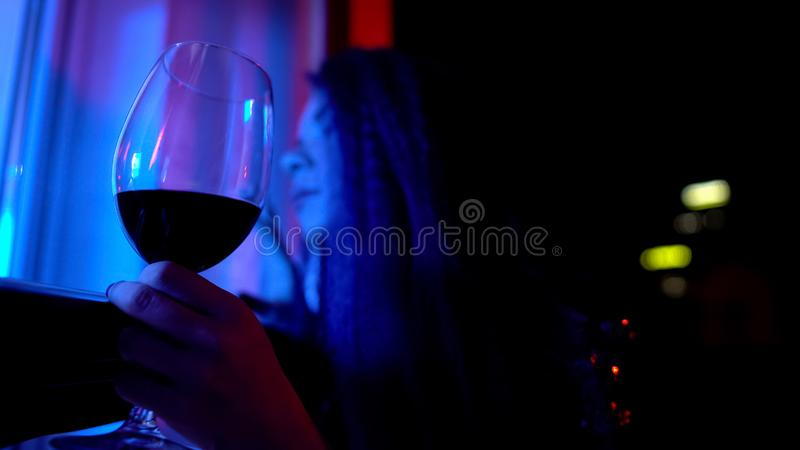 Drunk female falling asleep with glass of wine at balcony, alcohol addiction stock photo