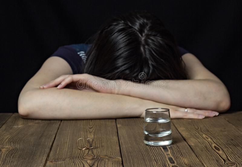 Drunk girl and alcohol on a wooden background, wedding rings on a table, divorce marriage royalty free stock photos