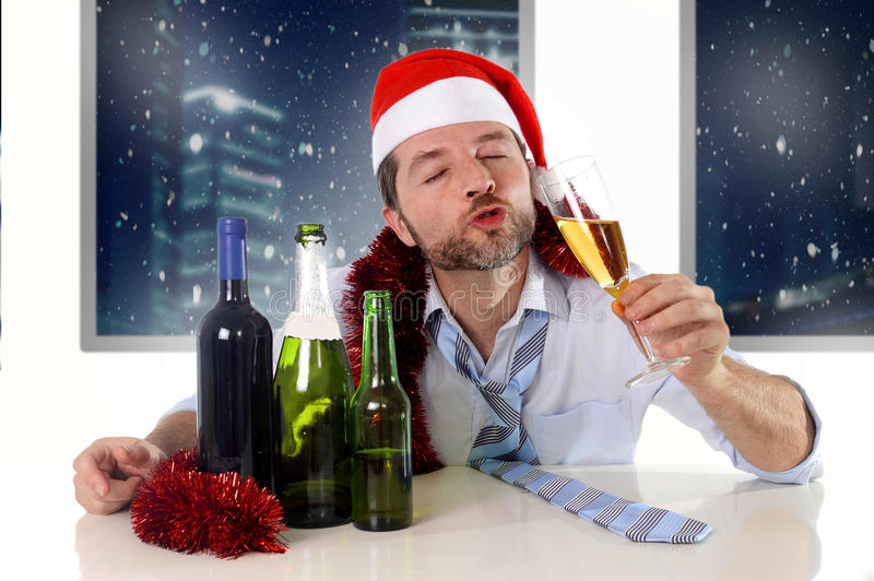 Drunk happy business man in Santa hat with alcohol bottles in new year toast with champagne glass royalty free stock image