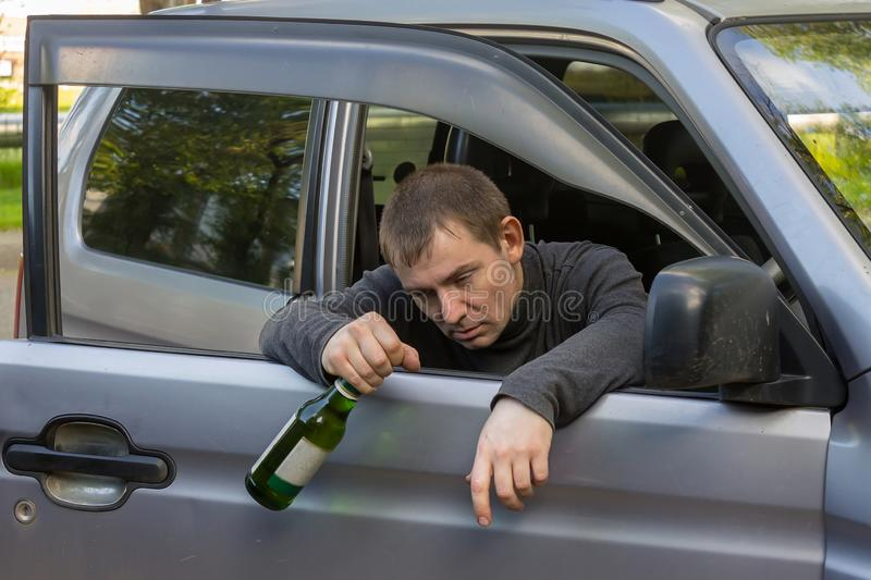 Irresponsible and drunk driver sleeps on the doors of his car with a bottle of alcoholic beverage. Drunk and irresponsible driver hanging on the doors of his car royalty free stock images