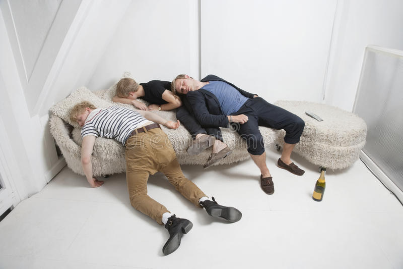 Drunk male friends sleeping on fur sofa after party stock photography