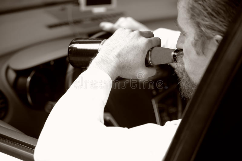 Drunk man in car with a bottle beer royalty free stock photos