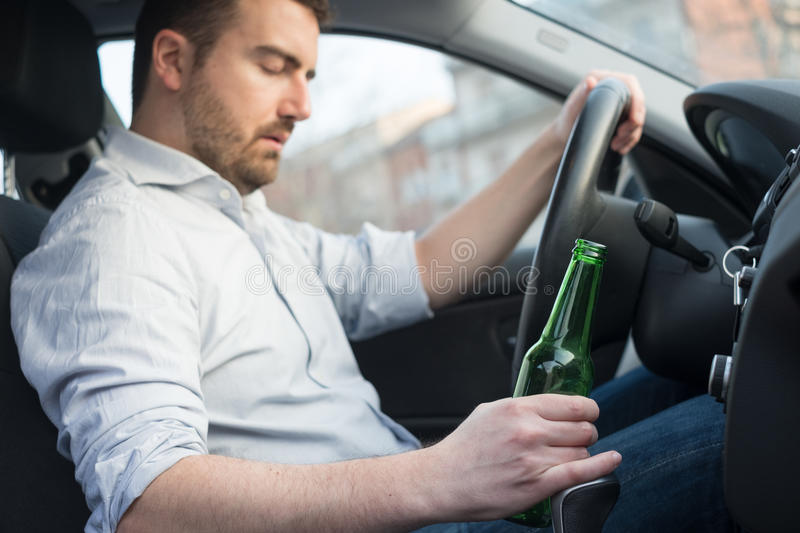 Drunk man driving car and falling asleep stock images