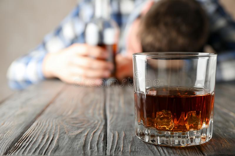 Drunk man holds bottle on wooden table with glass of whiskey stock photos