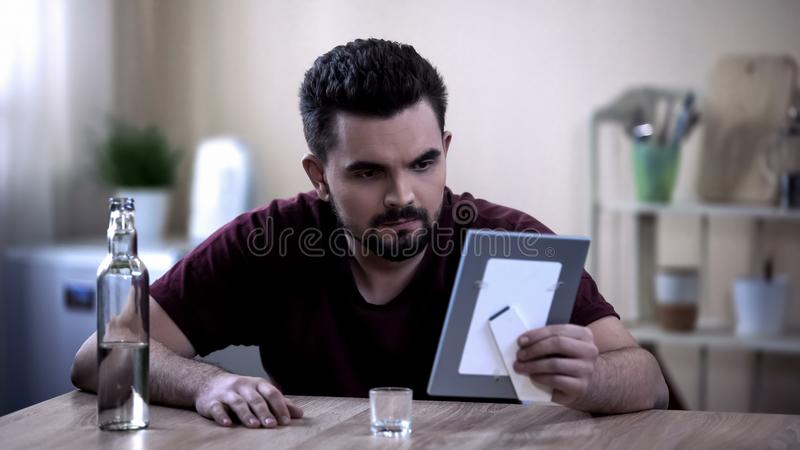 Drunk man looking at comrade-in-arms photo, suffering post traumatic syndrome royalty free stock images