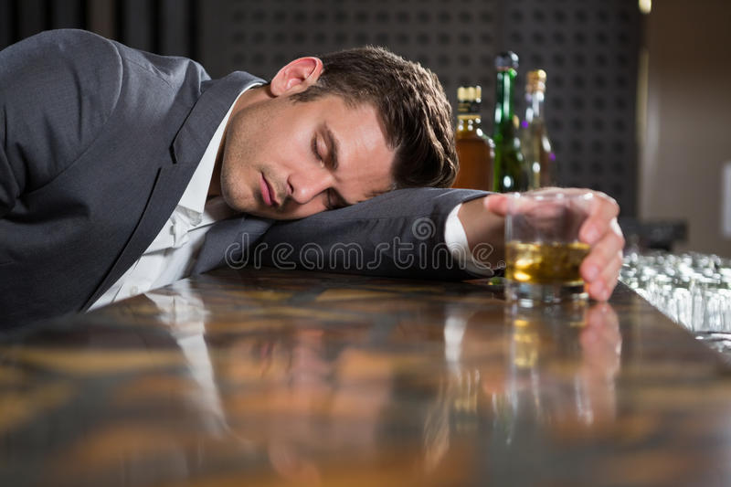 Drunk man lying on a counter with glass of whisky royalty free stock photography