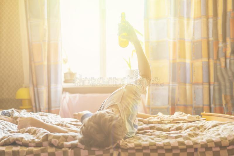 Drunk man lying at home with bottle of beer f royalty free stock photography