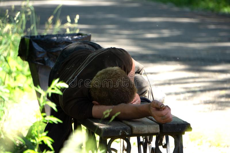 Drunk man sleeping in park on wooden bench stock image