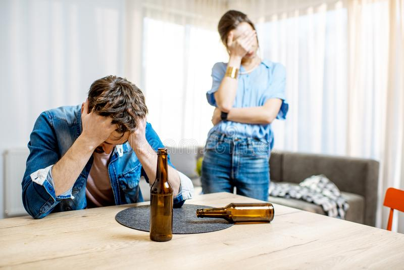 Drunk man with woman at home stock image