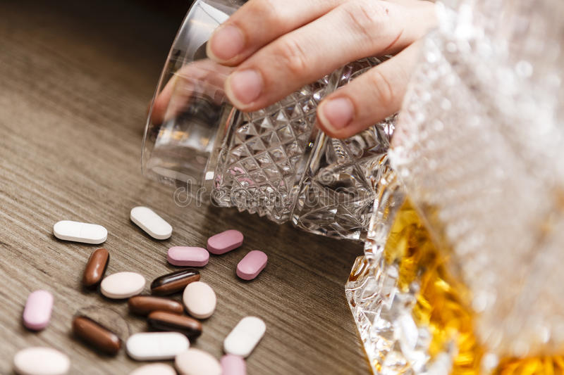 Drunk or poisoned young woman with bottle of alcohol and pills stock photography